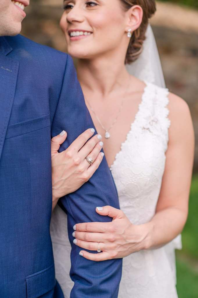 bride wrapping her arms around the left arm of the groom, detail of the lace Pronovias gown, as well as rings in focus