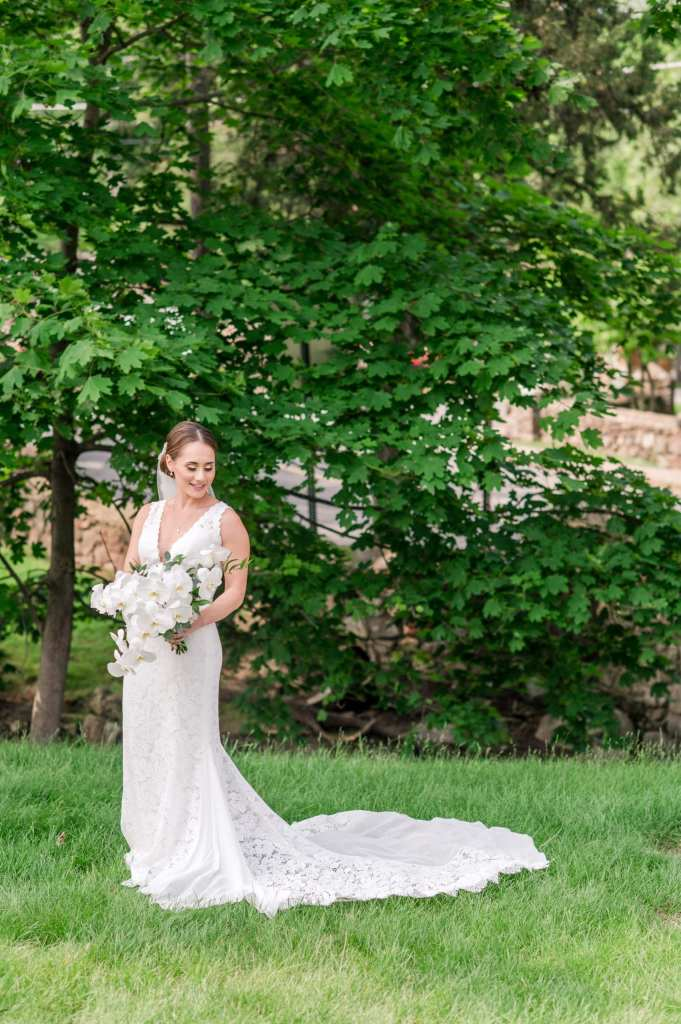Formal full length bridal portrait, bride in v-neck lace Pronovias gown, holding cascading white orchid bouquet by From Peonies to Paint Chips