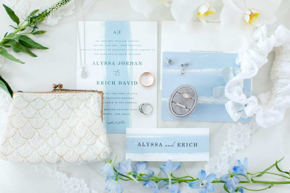 details of the wedding: white invitation with blue stripe down the middle, brides white beaded purse, family heirloom necklace and ring, brides earrings, engagement ring, wedding bands, family heirloom garter. All accented with light blue and white florals