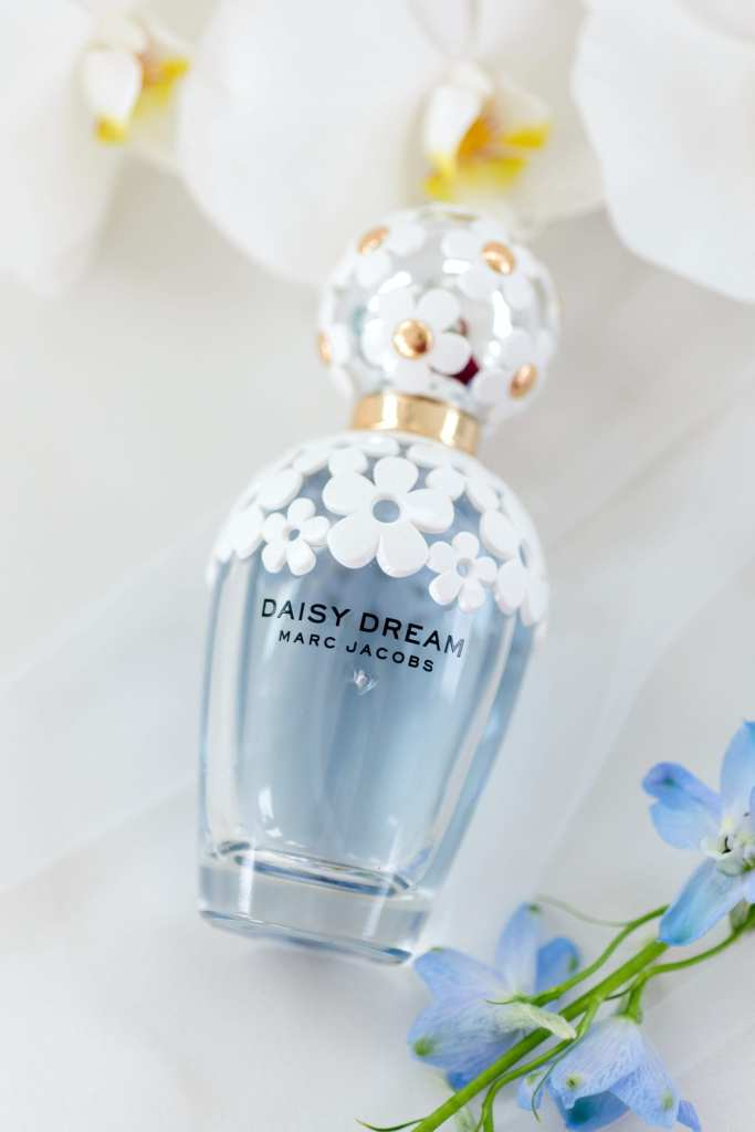 close up of bridal detail - brides bottle of Daisy Dream parfum by Marc Jacobs accented with white orchids and small blue floral