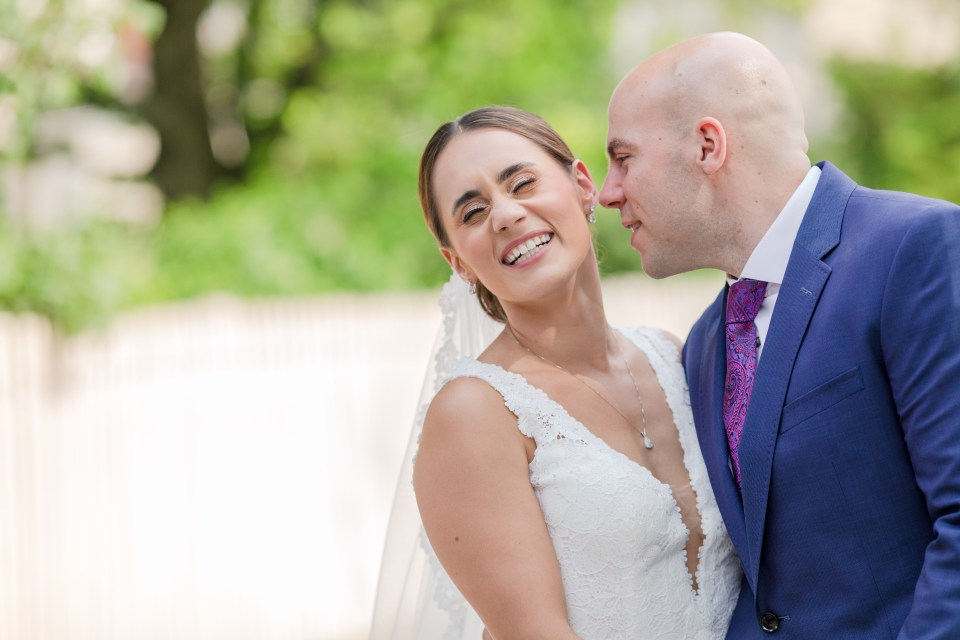 silly close up photo of bride in lace vneck gown grinning while the groom in navy blue suit by Jos. A. Banks whispers in her ear