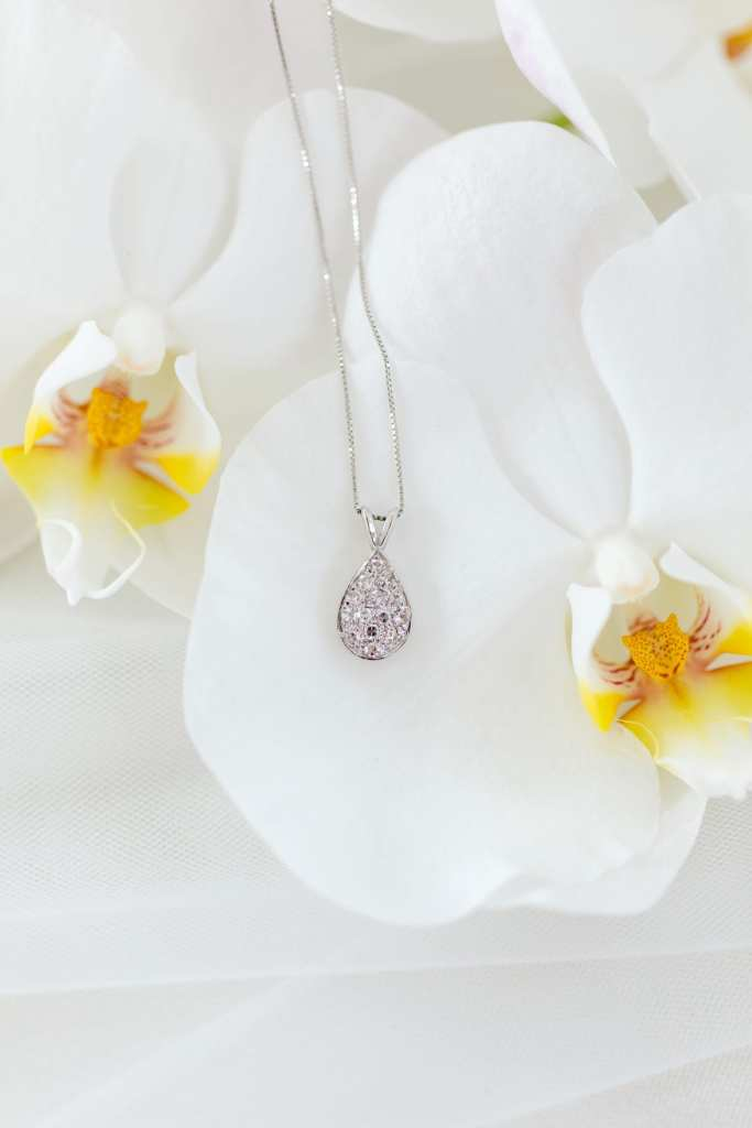 close up of the family heirloom diamond teardrop necklace set on top of white orchids in the bridal bouquet
