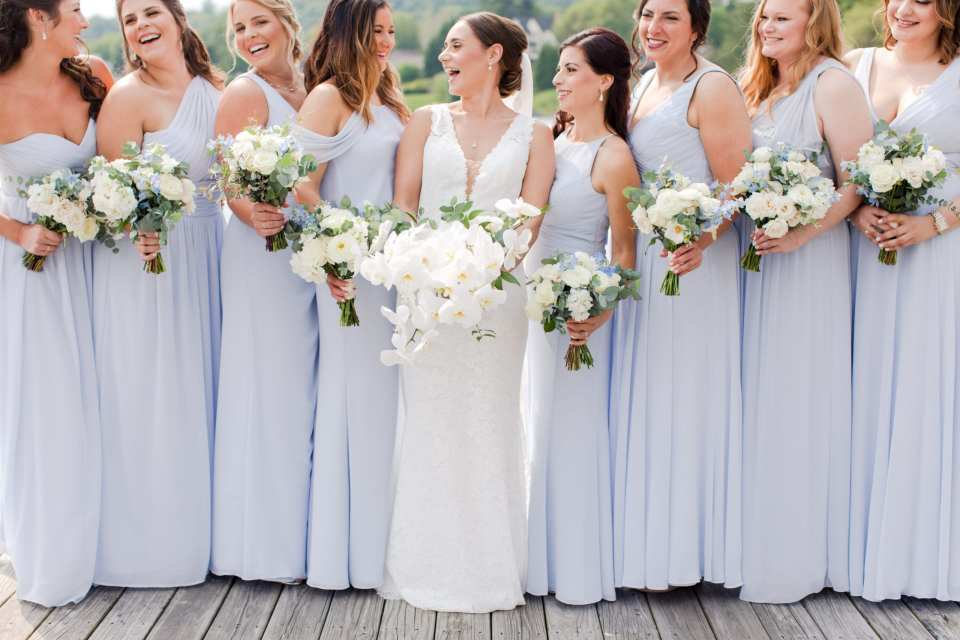 photo of the bride in v-neck lace gown by Pronovias surrounded by her bridal party in light blue floor length gowns by Watters