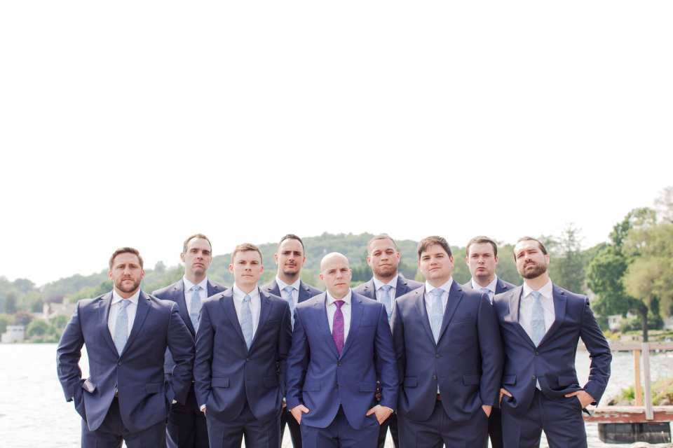 formal photo of the groomsmen with the groom in their navy blue Jos A. Banks suites, outdoors at the Lake Mohawk Country Club