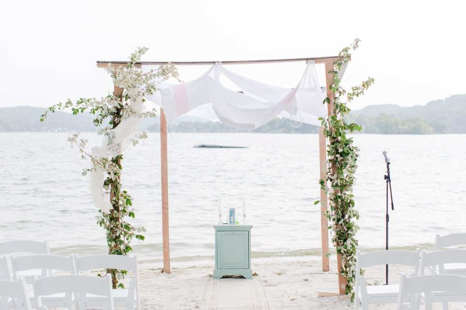 photo of the wooden chuppah covered with traditional prayer shawl and creeping greens in front of the lake at the Lake Mohawk Country Club