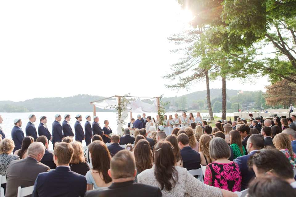 wide angle photo of the wedding ceremony in front of the lake at the Lake Mohawk Country Club, bridal party in light blue gowns by Watters, groomsmen in navy blue suits by Jos. A. Banks, bride in a gown by Pronovias. Bride and groom under traditional Chuppah with prayer shawl and creeping ivy on the wooden legs of the Chuppah