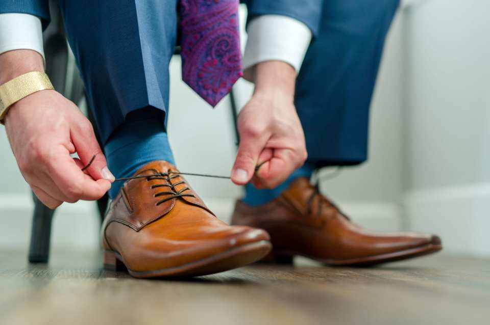 close up photo of groom tying the shoe lace on his brown shoes
