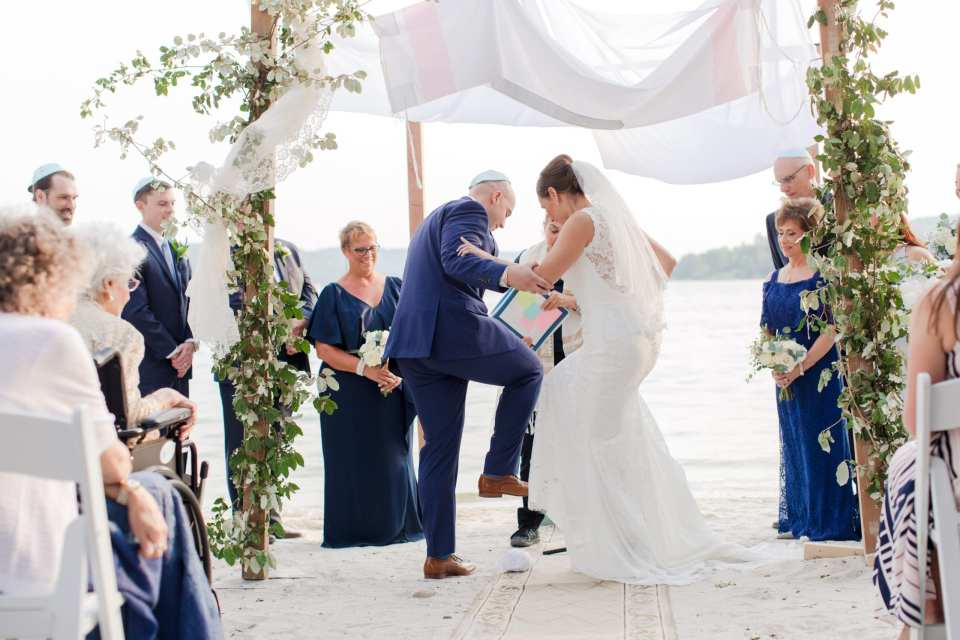 the bride and groom break the glass under a traditional chuppah, covered in traditional prayer shawl, with greens climbing the wood of the chuppah, against the lbackdrop of the lake at Lake Mohawk Country Club