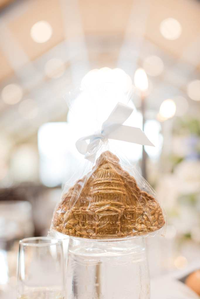 gold cookie favor in a bag tied with a white ribbon, displayed on a water glass