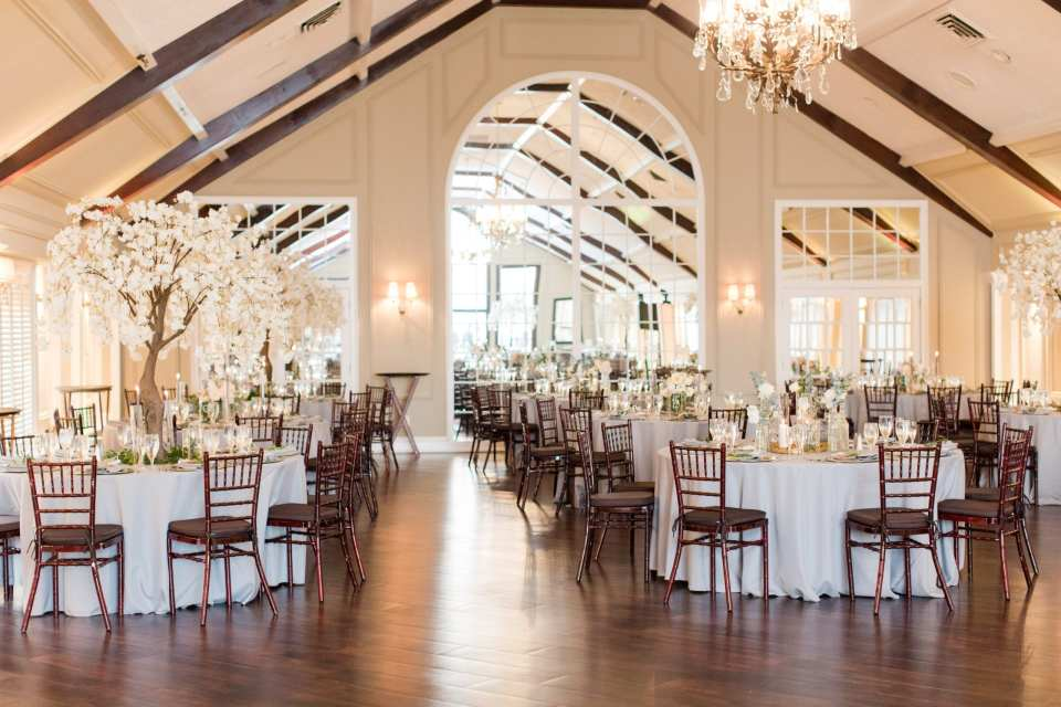 wide angle photo of the interior of the Lake Mohawk Country Club set up for a wedding reception with white linen tables and dark brown chivari chairs set with tall tree and white floral arrangements and low white floral arrangements from Peonies to Paint Chips