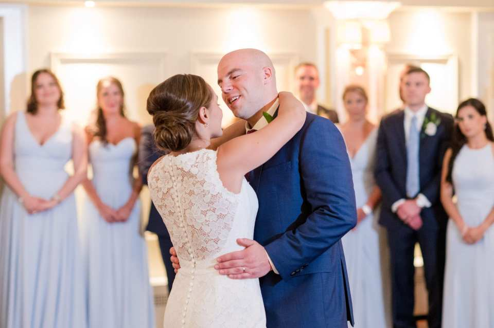Bride in Pronovias gown, Groom in navy blue Jos A Banks suit while dancing their first dance together, wedding party in background