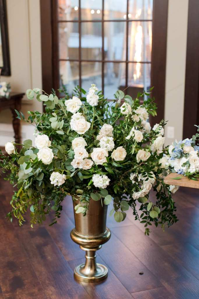 Large bronze floral urn filled with greens and white roses by From Peonies to Paint Chips