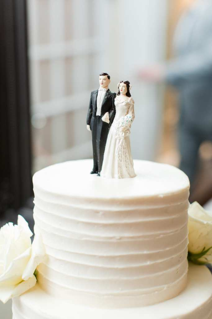 Vintage traditional bride and groom cake topper on the top tier of the three tier white wedding cake
