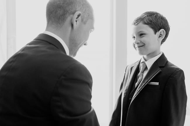 black and white photo groom and his young son get ready for the wedding in the grooms suite