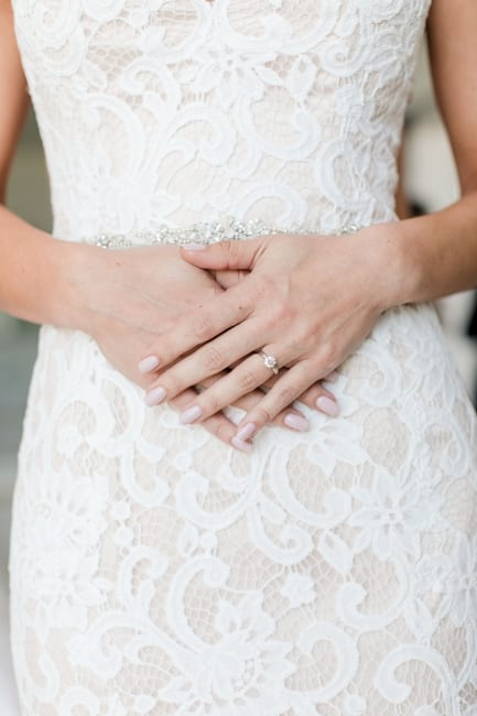 the brides hands crossed over her waist, highlighting her round diamond engagement ring, the lace on her gown and the stone waist band of the gown