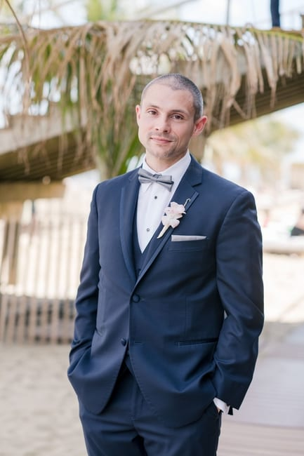 a formal portrait of the groom on the beach under the boardwalk as he waits for his bride during their first look