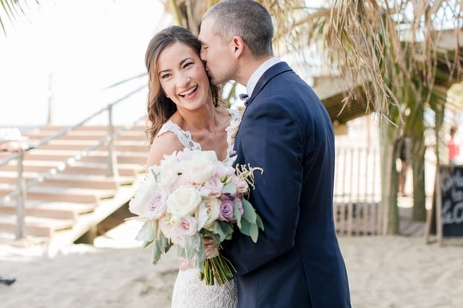half shot of bride and groom during their first look on the beach, the groom sneaking a kiss on the brides cheek