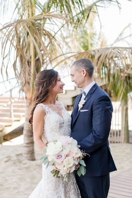 bride and groom on the beach for their first look, holding one another and the bridal bouquet, looking at one another