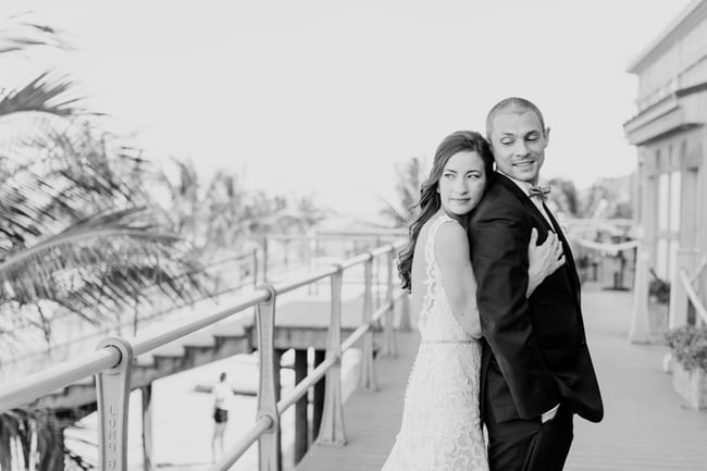 black and white photo of the bride behind her groom, arms wrapped around him, looking off towards the ocean from the boardwalk