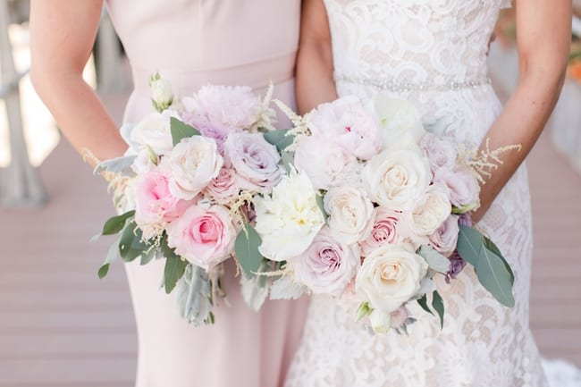 close up of the bridal bouquet of white, cream and blush peonies with some greens next to the maid of honors bouquet with more pink and purple florals with some greens