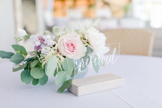 acrylic reserved sign in front of a small floral of lavendar, pink and white florals with greens