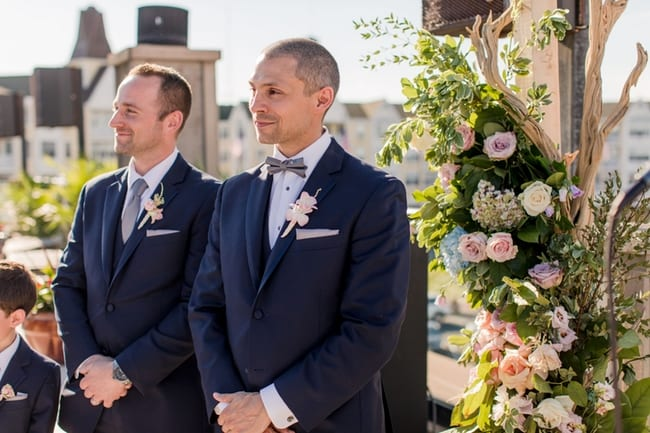 the groom and his best man look down the aisle at the bride as she makes her way to him at the floral altar