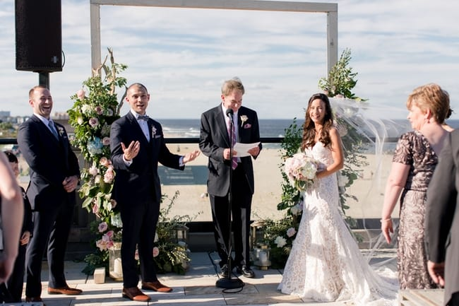 funny moment for the bride and groom during their ceremony outdoors overlooking the beach in front of a custom floral altar