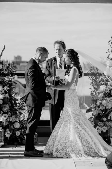 black and white photo of the bride and groom exchange vows overlooking the beach in front of custom floral altar pieces