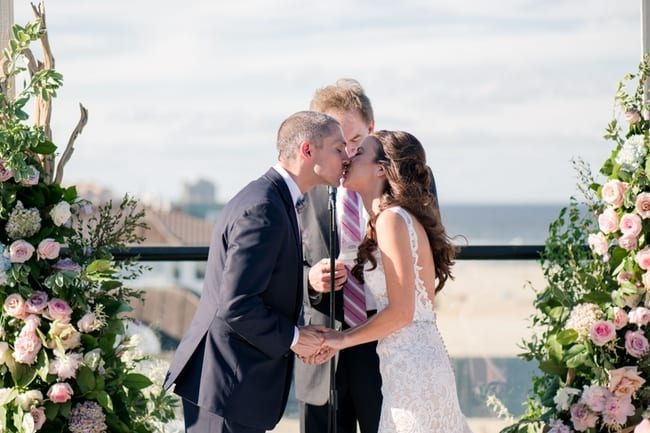 the bride and groom seal their vows with a kiss overlooking the beach in front of custom floral altar pieces