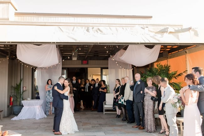 wide angle photo of the bride and groom during their first dance on a tiled patio being watched by guests standing