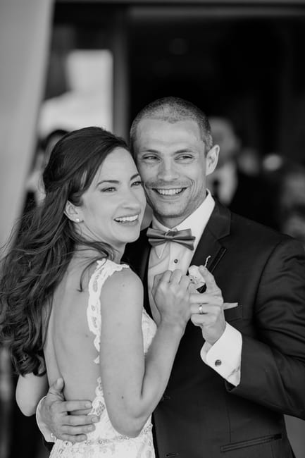 black and white candid photo of the bride and groom during their first dance