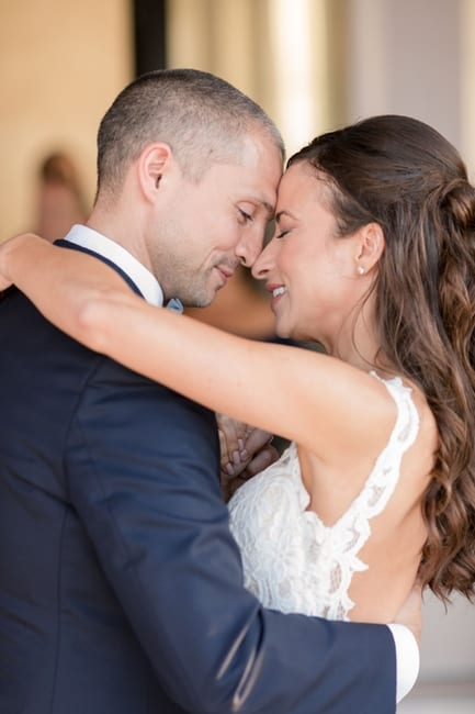 the bride and groom forehead to forehead during their first dance