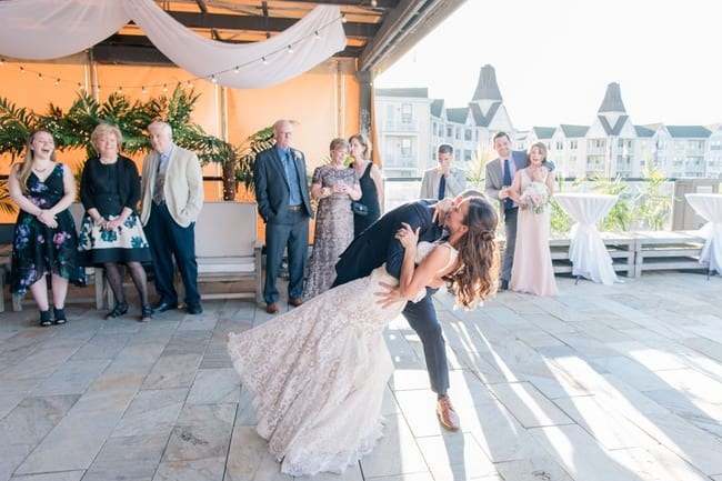 a wide angle view of the groom dipping his bride during their first dance