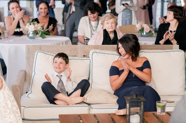 A fun photo of the grooms sister and the grooms son sitting next to each other and clapping