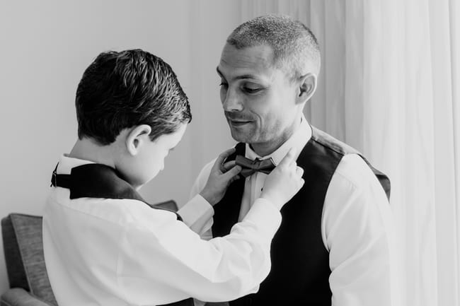 black and white photo of grooms son adjusting the grooms bowtie in the grooms suite