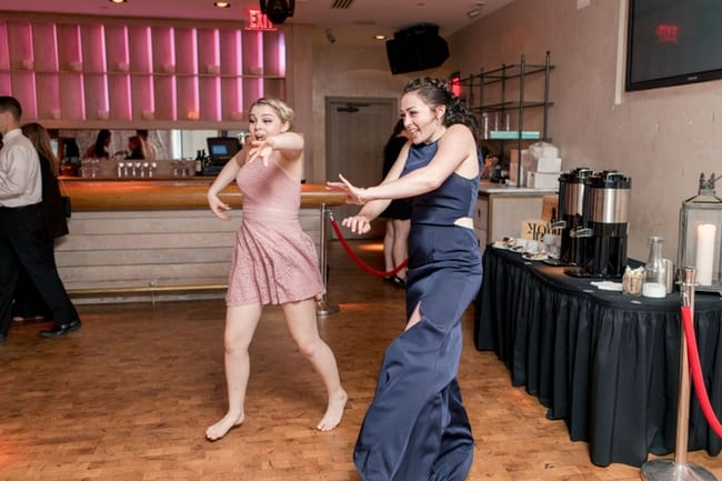 Two wedding guests have a very fun time dancing during the wedding reception
