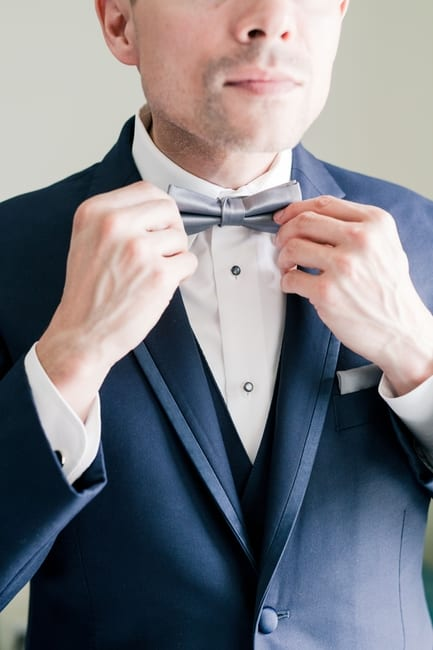 close up of groom in navy blue tuxedo adjusting his grey bowtie