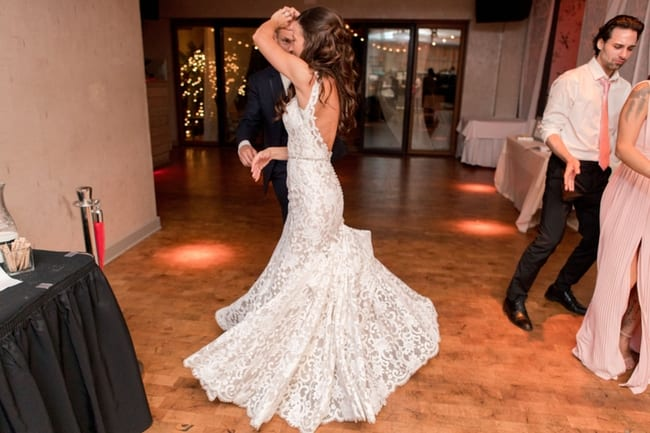 the bride being spun in her wedding gown during a dance with her husband during the wedding reception