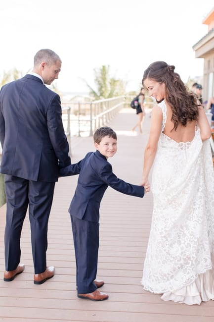 A photo of the bride and groom on the boardwalk from the back, with the grooms young son in between them, he turning around to look at the camera