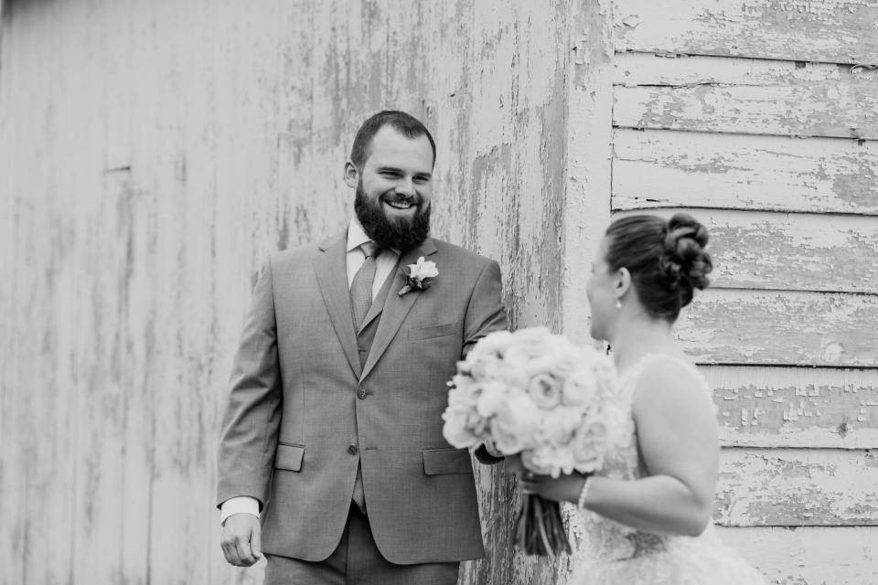 black and white photo of the grooms face as he sees his bride come around the corner of an aged white washed barn building at the Updike Farmstead for their first look