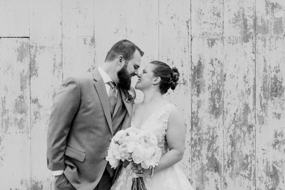 black and white photo of the bride and groom nose to nose, grinning, during the first look outside a white washed barn