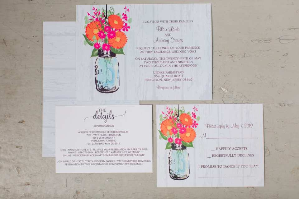 display of the wedding invitation suite which has a digital mason jar with brightly colored flowers in it over a lightly whitewashed barn wall print