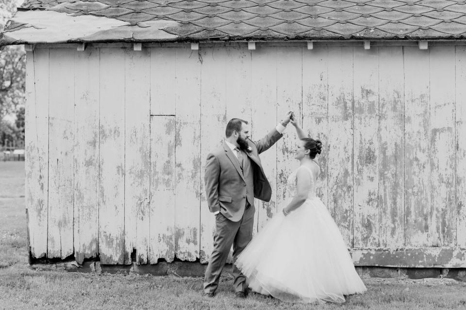 black and white photo of the groom twirling his bride outside of a small barn at the Updike Farmstead