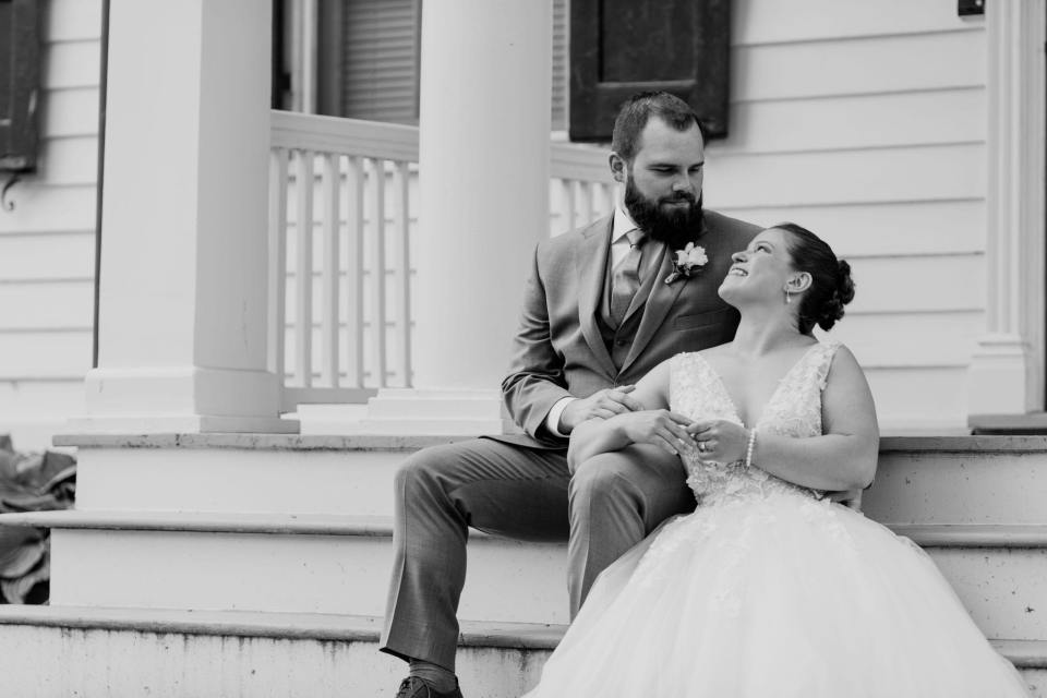 black and white photo of the bride and groom looking at one another while sitting on the front steps of the farmhouse at the Updike Farmstead
