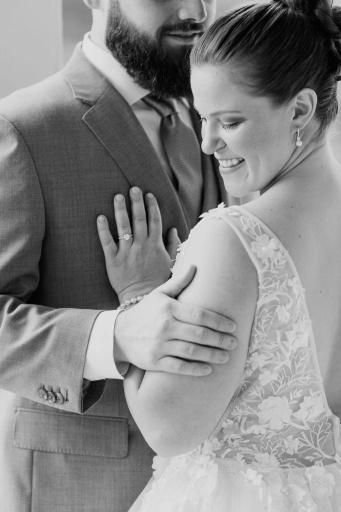 black and white photo of the bride from behind, being held by her groom, gazing over her left shoulder towards the camera, smiling