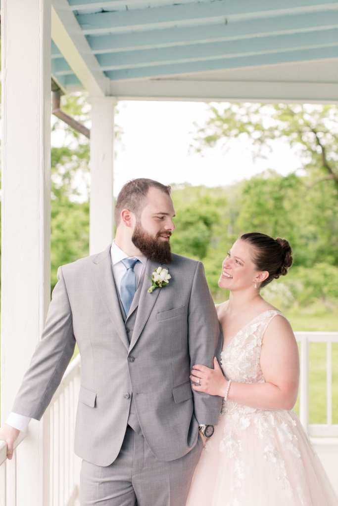 bride in her pink tulle v-neck wedding gown holding onto the grooms arm, standing next to him, while looking at each other on the porch of the farmhouse of the Updike Farmstead