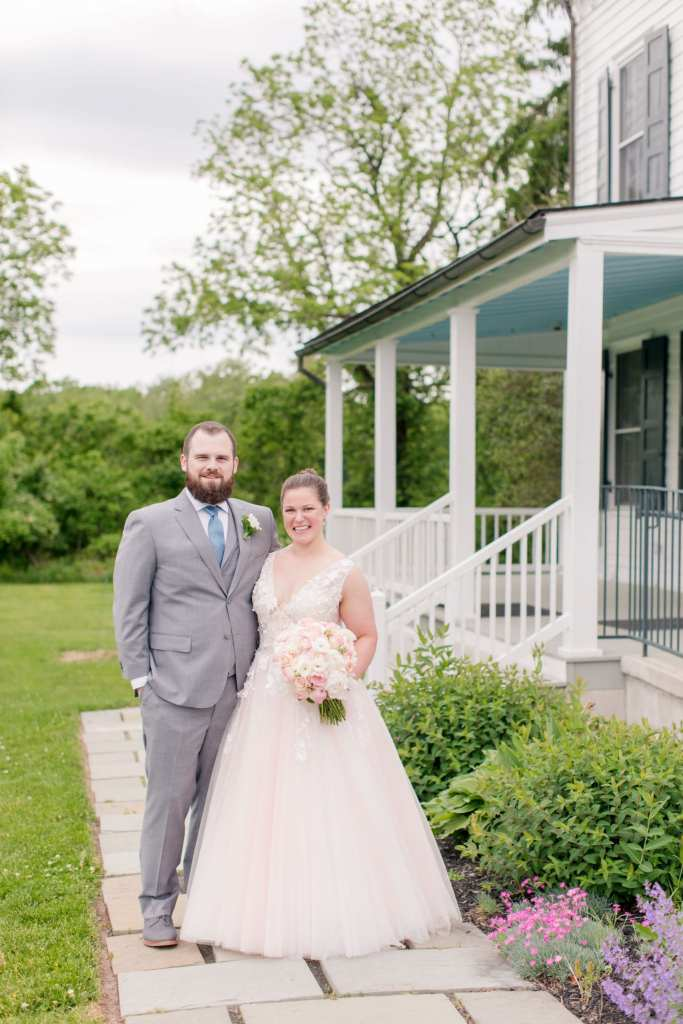 bride and groom formal portrait standing side by side, arms wrapped around the others waist in front of the porch of the main house at the Updike Farmstead