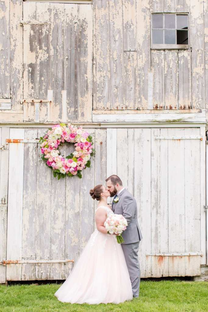 bride and groom holding one another, noses touching, in front of the white washed barn ceremony location at the Updike Farmstead with large floral wreath of various shades of pinks and ivories by the Flower Shop of Pennington Market