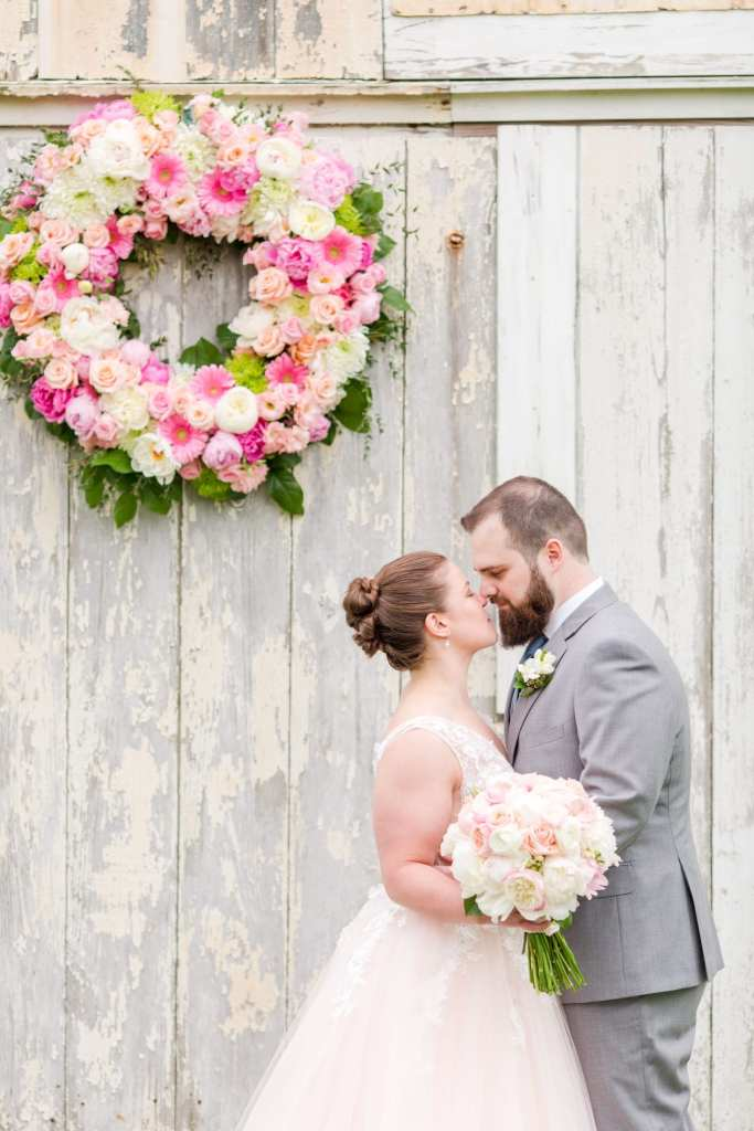 bride and groom holding one another, noses touching, in front of the white washed barn ceremony location with large floral wreath