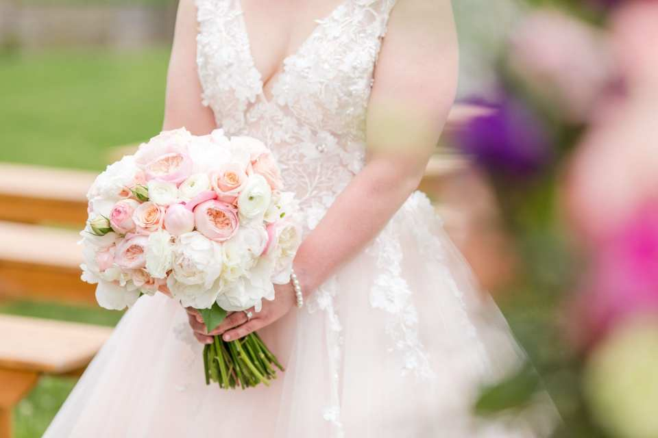 shot of brides waistline where she has her tied bridal bouquet of blush and cream florals